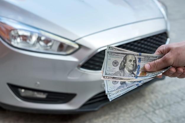 Zakenman geeft geld om een auto te huren voor zomervakantie. financieel concept