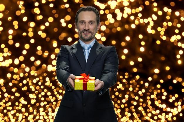 Zakenman geeft gele geschenkdoos met rood lint. zelfverzekerde senior manager feliciteert u met kerstmis. veel lichten op de achtergrond.