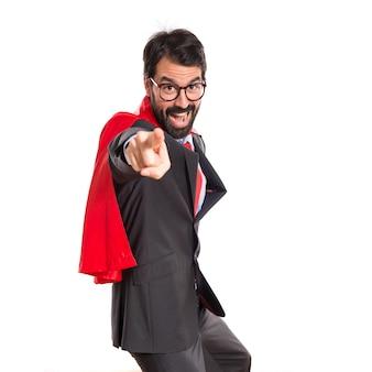 Zakenman gekleed als superheld die naar voren wijst