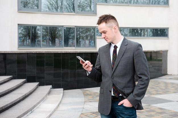 Zakenman, gekleed in een grijze jas, blauwe spijkerbroek, wit overhemd en stropdas komt uit het zakencentrum en praat tijdens het lopen aan de telefoon