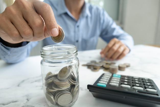 Zakenman geld besparen concept. hand met munten die in het glas van de kan doen