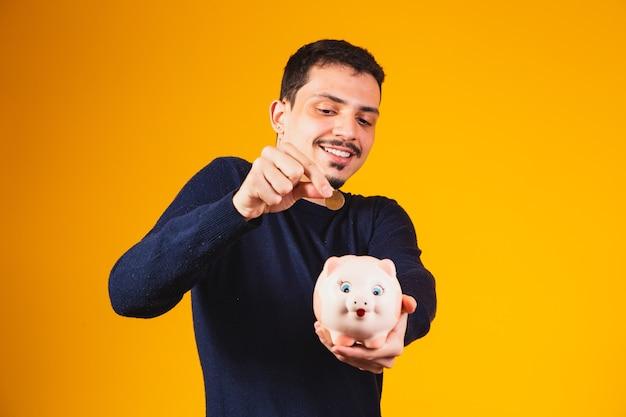 Zakenman geld besparen door munten in spaarvarken te zetten. jonge jongen met spaarvarken die munten deponeert
