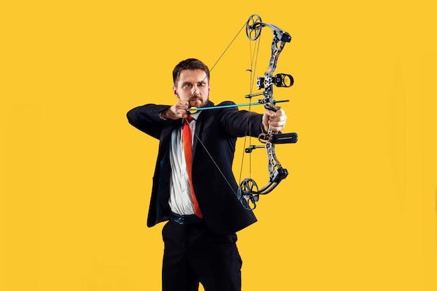 Zakenman gericht op doel met pijl en boog, geïsoleerd op gele studio achtergrond. het bedrijf, het doel, de uitdaging, de concurrentie, het prestatieconcept