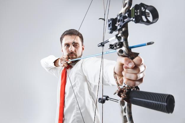 Zakenman gericht op doel met pijl en boog, geïsoleerd op grijze studio achtergrond. het bedrijf, het doel, de uitdaging, de concurrentie, het prestatieconcept