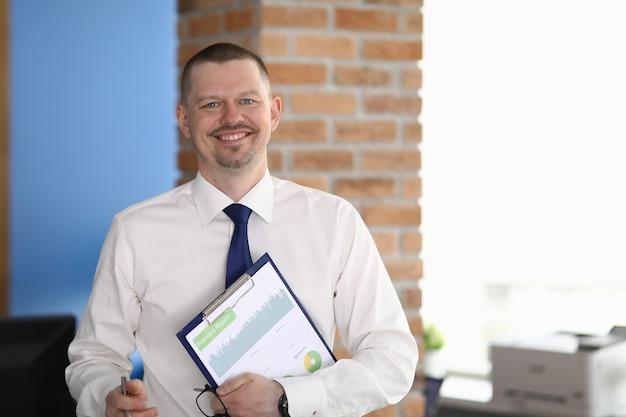 Zakenman glimlacht en houdt grafieken met zakelijke cijfers. bedrijfsontwikkeling consulting concept