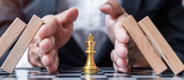 Zakenman hand beschermen chess king figuur en stoppen vallende houten blokken of dominostenen.