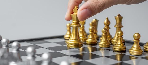 Zakenman hand gouden schaak koning figuur verplaatsen tijdens schaakbord concurrentie.