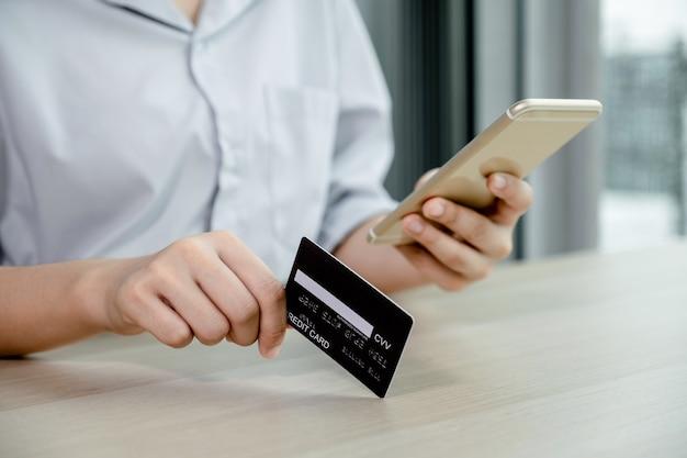 Zakenman hand houden creditcard voor online winkelen op smartphone vanuit huis, betaling e-commerce, internetbankieren, geld uitgeven voor de volgende vakantie.