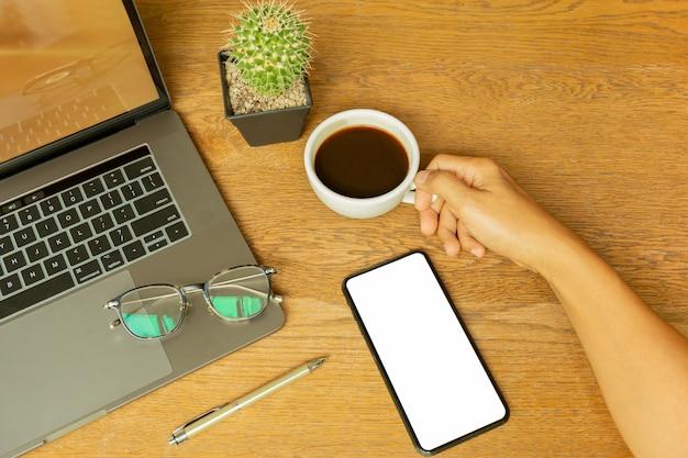 Zakenman hand houden koffiekopje met laptop en eyeglasson houten bureau.