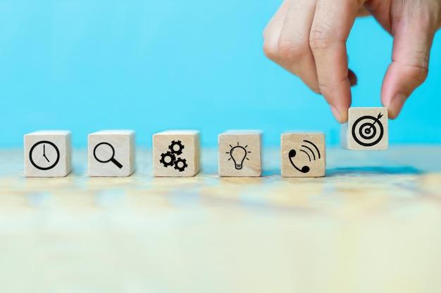 Zakenman hand hout blok met pictogram bedrijfsstrategie regelen