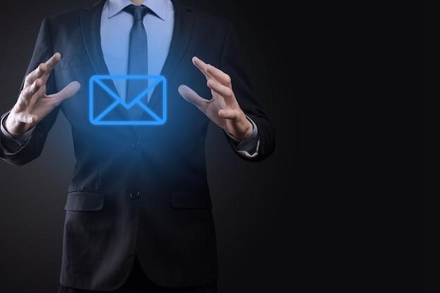 Zakenman hand met e-mailpictogram, neem contact met ons op via nieuwsbrief e-mail en bescherm uw persoonlijke gegevens tegen spam-e-mail. klantenservice callcenter contacteer ons concept