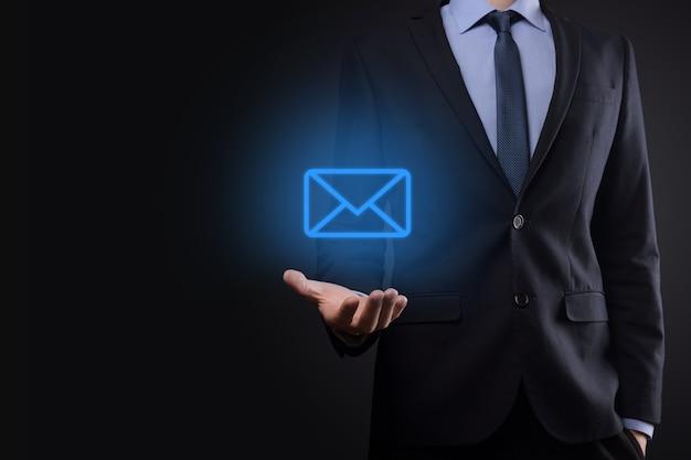 Zakenman hand met e-mailpictogram, neem contact met ons op via nieuwsbrief e-mail