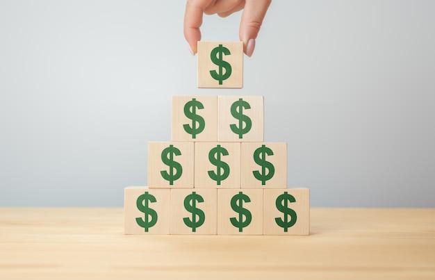 Zakenman hand met houten blokken met het symbool van de amerikaanse dollar. geld, contant geld, valuta en investeringsconcept. bedrijfsgroei, winst verhogen, inkomen verhogen of concept sparen.