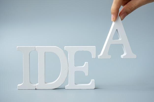 Zakenman hand met houten ideeën tekst op grijs. nieuw creatief, innovatie, verbeelding, inspiratie, oplossing, strategie en doelconcept
