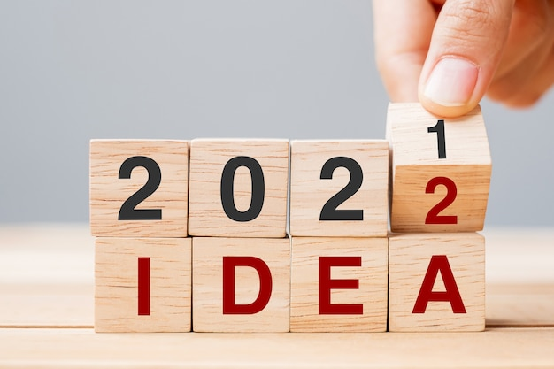 Zakenman hand met houten kubus en flip-over blok 2021 tot 2022 idee op tafel achtergrond. resolutie, plan, trend, verandering, start en nieuwjaarsvakantieconcepten