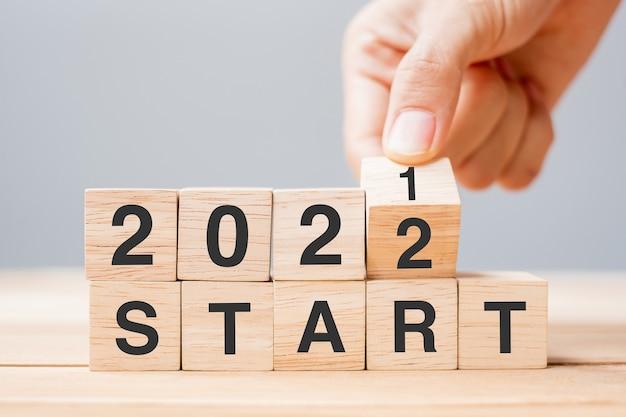 Zakenman hand met houten kubus en flip-over blok 2021 tot 2022 start op tafelachtergrond. resolutie, plan, beoordeling, verandering, doel en nieuwjaarsvakantieconcepten