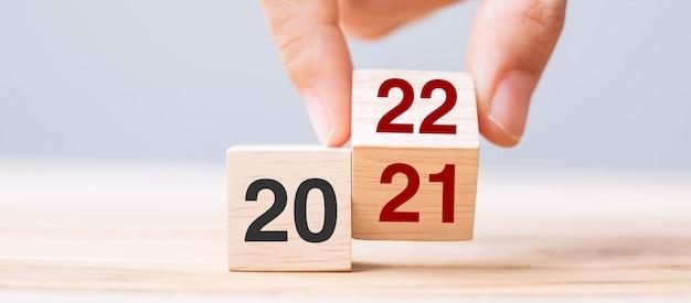 Zakenman hand met houten kubus met flip-over blok 2021 tot 2022 tekst op tafel achtergrond. resolutie, strategie, oplossing, doel, zakelijke en nieuwjaarsvakantieconcepten