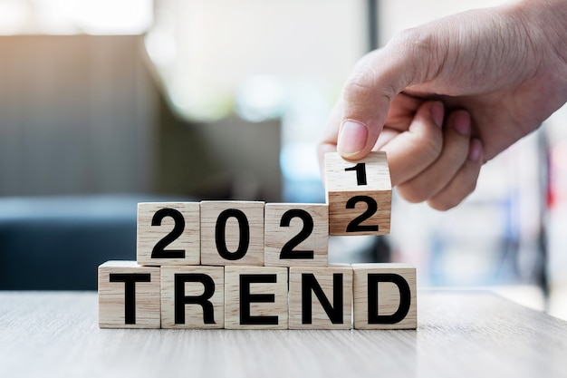 Zakenman hand met houten kubus met flip-over blok 2021 tot 2022 trend woord op tafel achtergrond. resolutie, strategie, oplossing, doel, zakelijke en nieuwjaarsvakantieconcepten