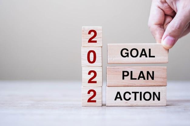 Zakenman hand met houten kubus met tekst 2022 doel, plan en actie op tabelachtergrond. resolutie, strategie, oplossing, doel, zakelijke en nieuwjaarsvakantieconcepten