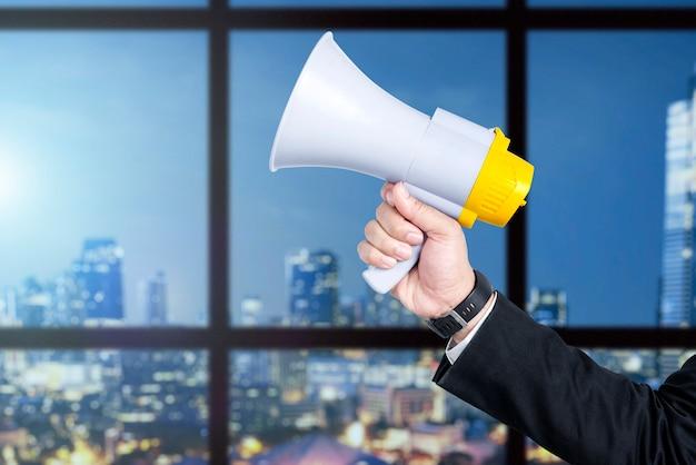 Zakenman hand met megafoon met kantoorgebouw achtergrond