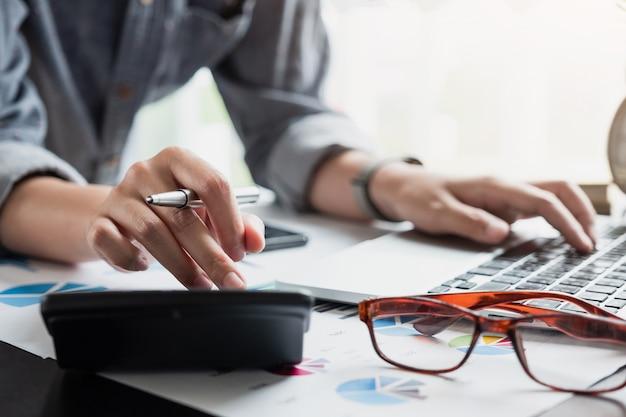 Zakenman hand met pen bezig met rekenmachine om zakelijke gegevens te berekenen.