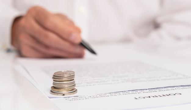 Zakenman hand met pen over document close-up. geldmunten in focus op voorgrond