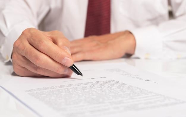 Zakenman hand met pen over document close-up.