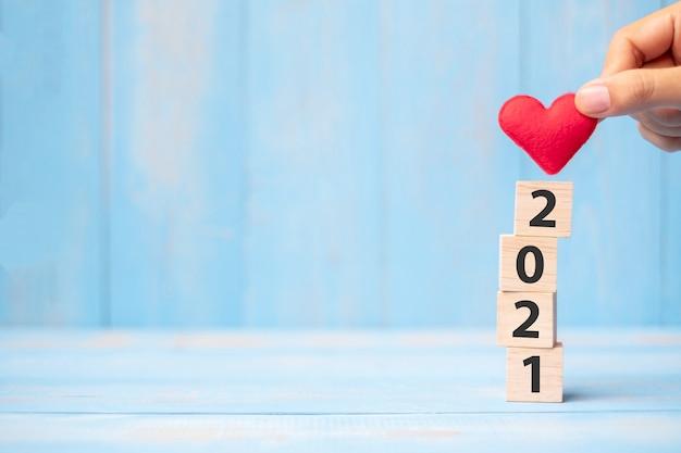 Zakenman hand met rood hart vorm over 2021
