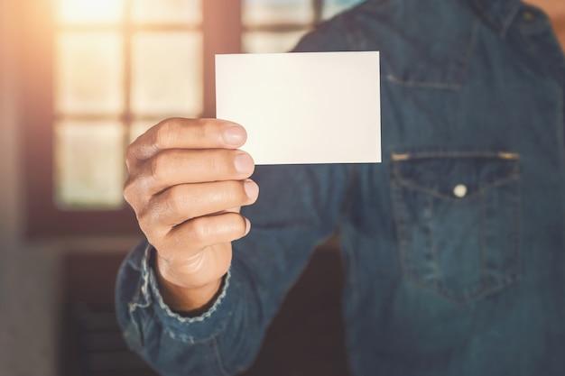 Zakenman hand met visitekaartje in kantoor met zonneschijn