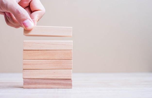 Zakenman hand plaatsen of trekken houten blok op de toren.