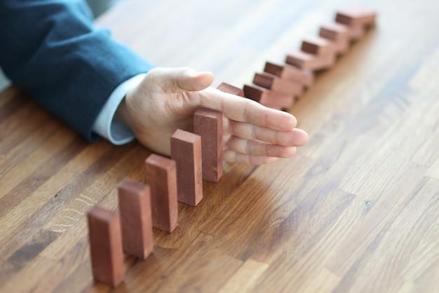 Zakenman hand scheidt houten blokken op tafel