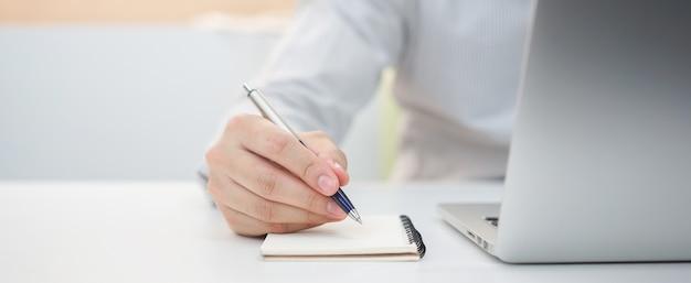 Zakenman hand schrijven inhoud of iets op laptop