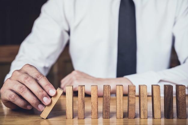 Zakenman hand stoppen vallende houten domino's effect van continu omvallen of risico