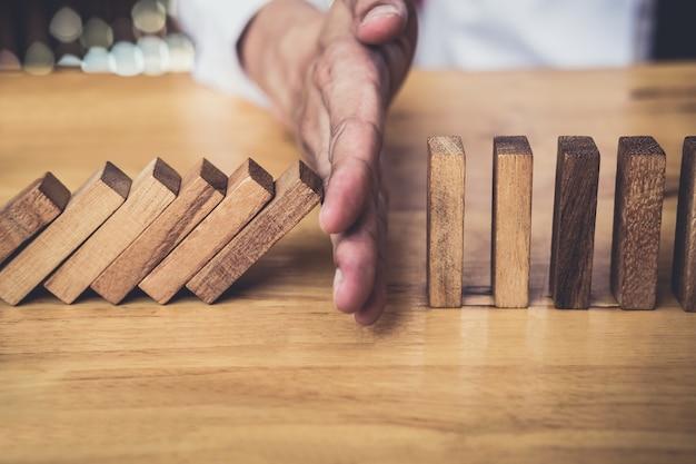 Zakenman hand stoppen vallende houten domino's effect van continu omvallen of risico.
