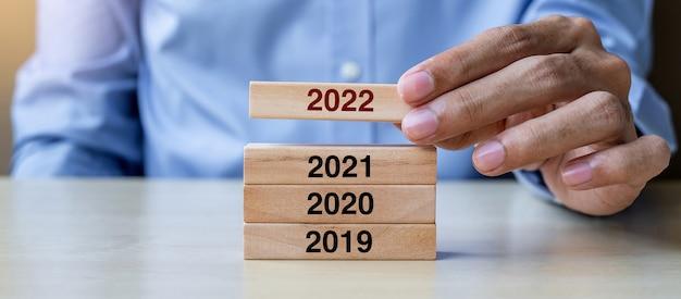 Zakenman hand trekken 2022 houten bouwstenen op tabelachtergrond. bedrijfsplanning, risicobeheer, resolutie, strategie, oplossing, doel, nieuwjaar, nieuwe jij en gelukkige vakantieconcepten
