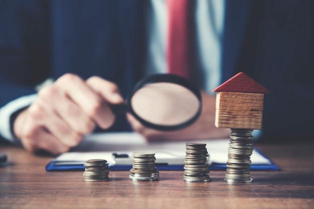 Zakenman hand vergrootglas document met munten en huis model