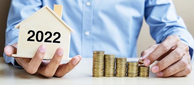 Zakenman hand zetten gouden munt met 2022 houten huis