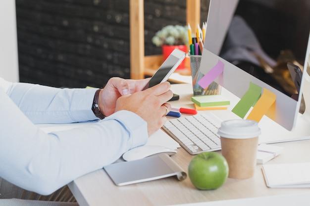 Zakenman handen bezig met behulp van mobiele telefoon op kantoor