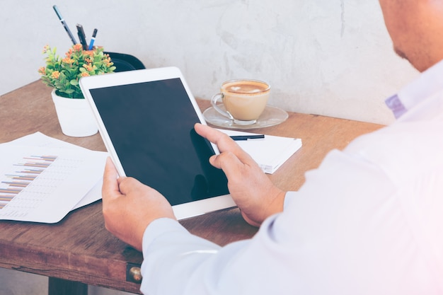 Zakenman handen op een tafel met een tablet en een kopje koffie in een kantoor