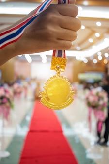 Zakenman handen opgewekt en gouden medailles met thaise lint tegen conventiezaal achtergrond om succes te zien in het bedrijfsleven, winners succes award concept.