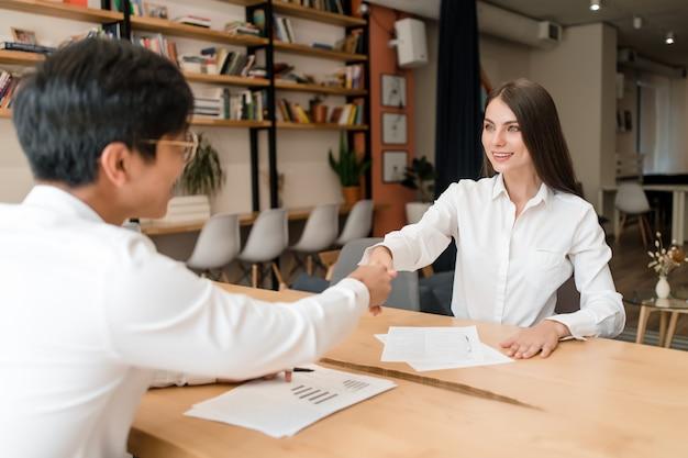 Zakenman handen schudden op een deal met jonge zakenvrouw in de conferentiezaal van het kantoor