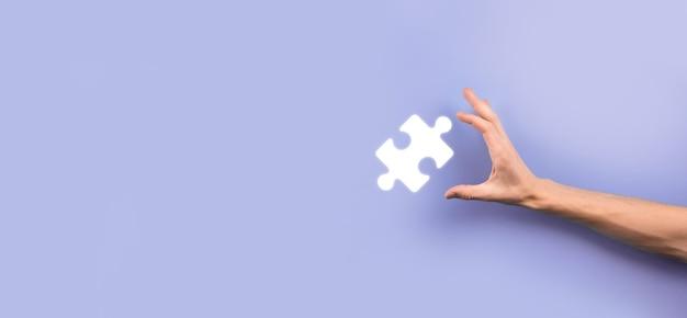 Zakenman handen verbinden puzzelstukjes die de fusie van twee bedrijven of joint venture, partnerschap, fusies en overname concept vertegenwoordigen.