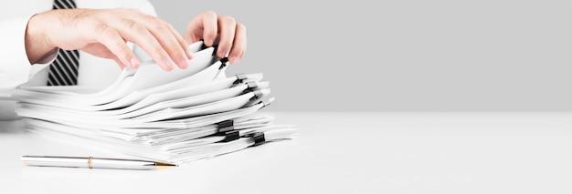 Zakenman handen werken in stapels papieren bestanden op zoek naar informatie