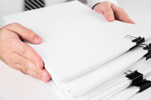 Zakenman handen werken in stapels papieren dossiers voor het zoeken naar informatie