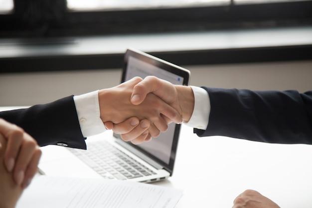 Zakenman handshaking zakenvrouw toont respect, close-up weergave van handen schudden