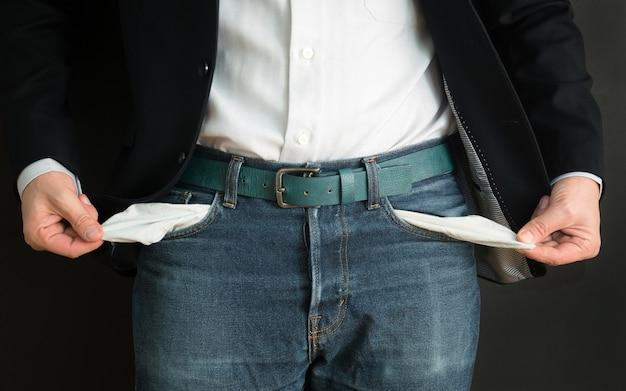 Zakenman heeft geen geld. werkloze en failliete man kijkt in zijn lege zakken.
