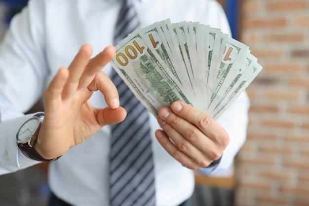 Zakenman heeft honderd dollarbiljetten in zijn hand met secondewijzer toont het gebaar ok.