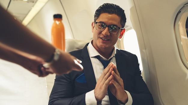 Zakenman heeft sinaasappelsap geserveerd door een stewardess in vliegtuig