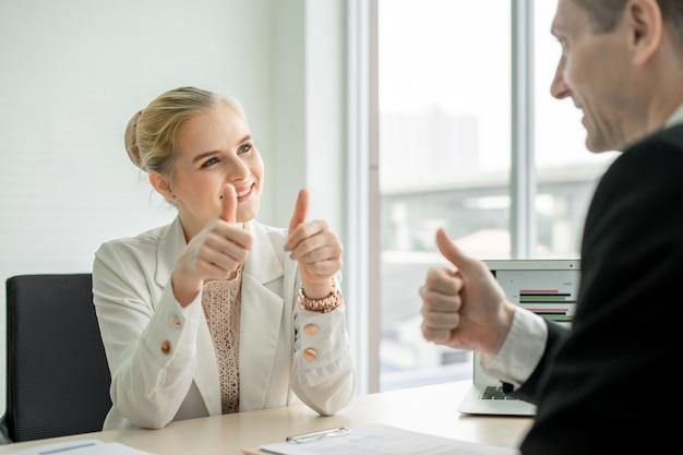 Zakenman het doen beduimelt omhoog gelukwens aan vrouw bij bureau in bureauruimte