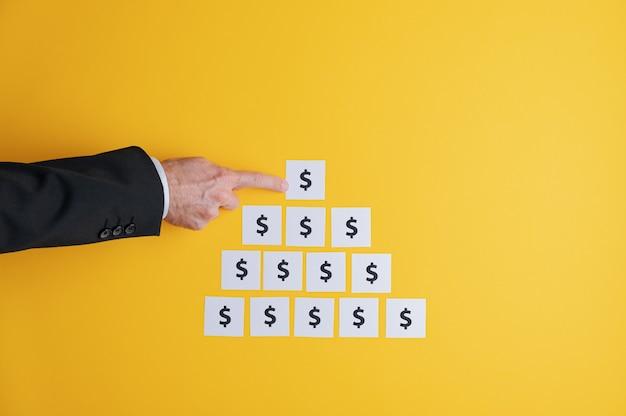 Zakenman het maken van een piramidevormige stichting van witte post-it papieren met dollarteken erop in een conceptueel beeld van winst en macht. over gele achtergrond met kopie ruimte.